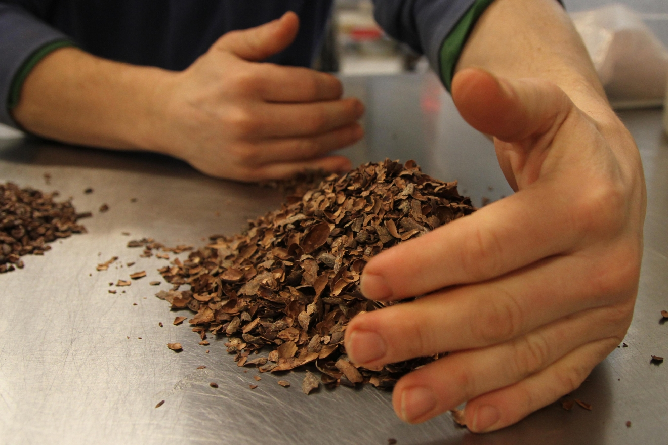 Adam sweeps up some of the separated cacao shells. (Image: Amanda Andrade-Rhoades/ DC Refined)