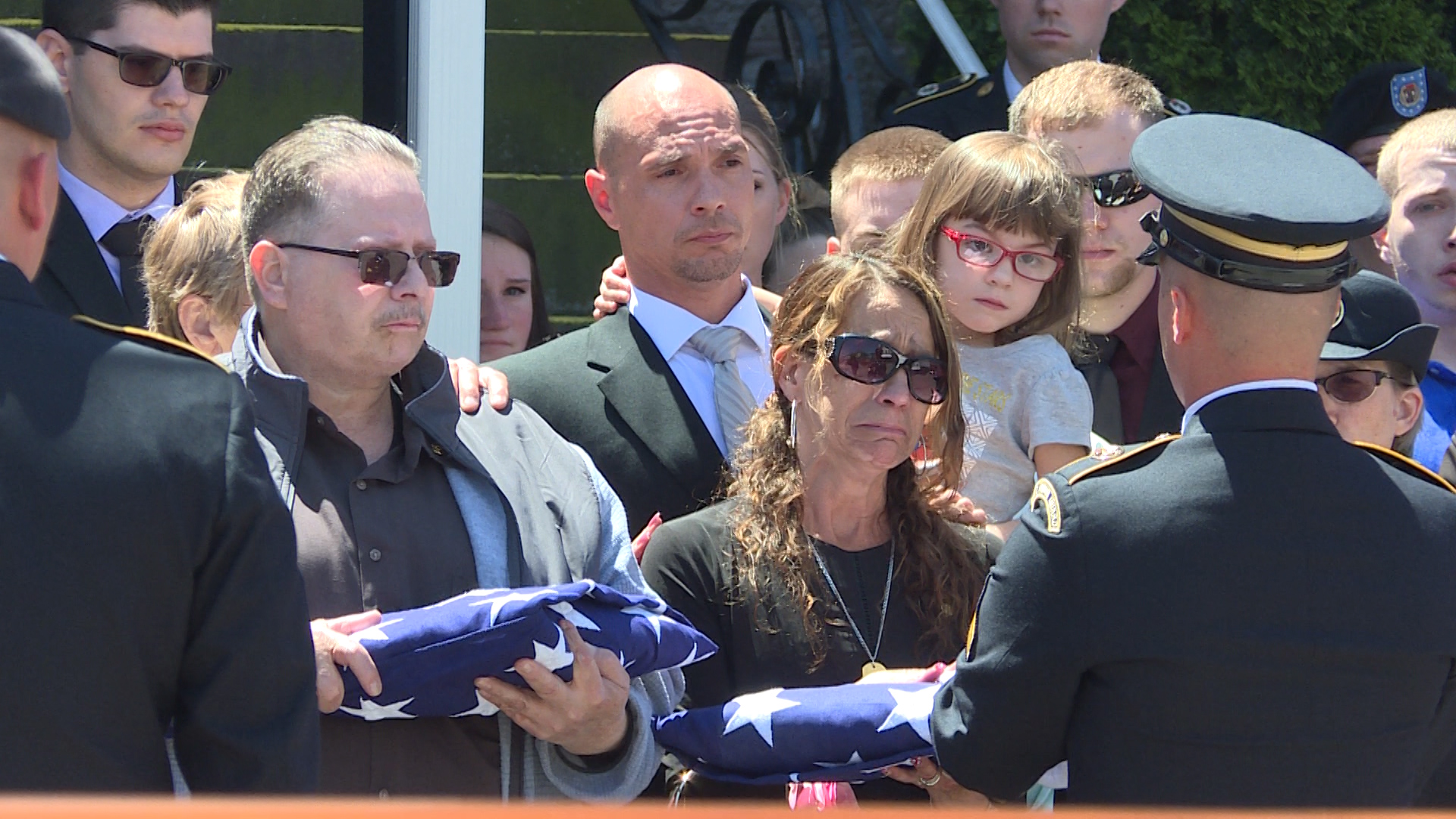 Both Luddy's parents receive an American flag.{ }