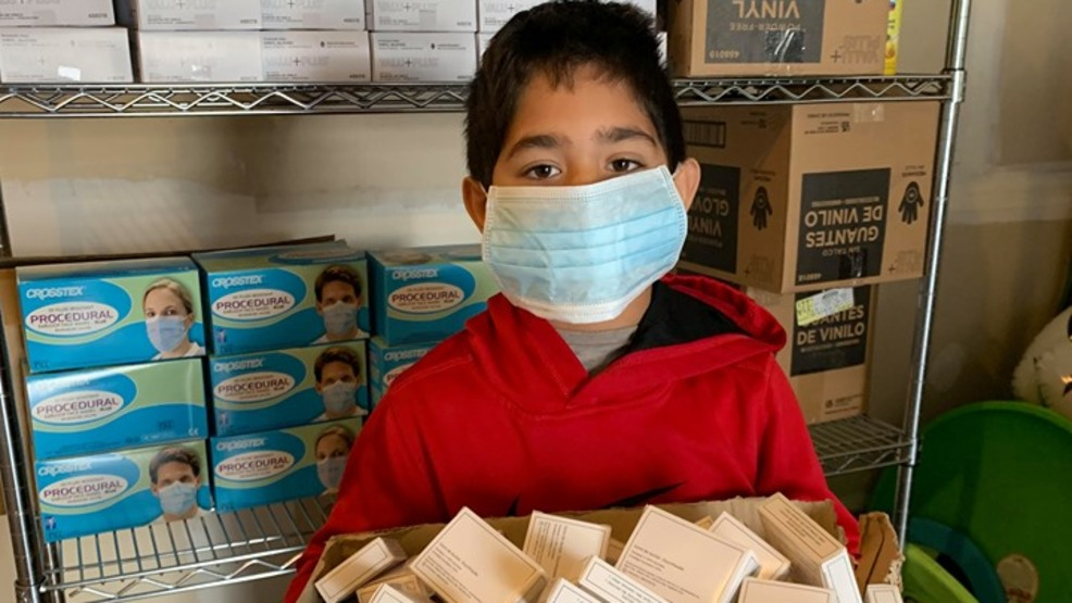 A boy in a red sweatshirt with a protective mask over his face surrounded by boxed masks.