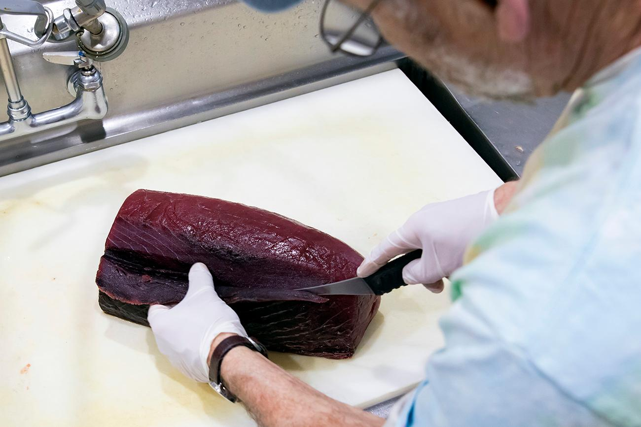 Owner Kevin Smith cutting tuna steaks{ }/ Image: Allison McAdams // Published: 3.11.19