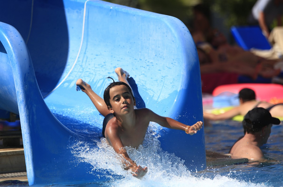 A child enjoys a water slide on a beach near the coastal town of Bodrum, Turkey, Sunday, Aug. 16, 2015. The city of Bodrum, a magnet for wealthy tourists, is these days drawing plenty of other visitorsó migrants fleeing conflicts in the Middle East and Africa and seeking a better life in Europe. At its closest point, the Greek island of Kos is only 4 kilometers (2.5 miles) from Turkey and migrants, mostly from Syria, but also from Afghanistan, Iran and African nations often try to cross in groups upward of eight people in small inflatable plastic boats meant for a maximum of four, powered by tiny electric outboard motors and plastic paddles. (AP Photo/Lefteris Pitarakis)