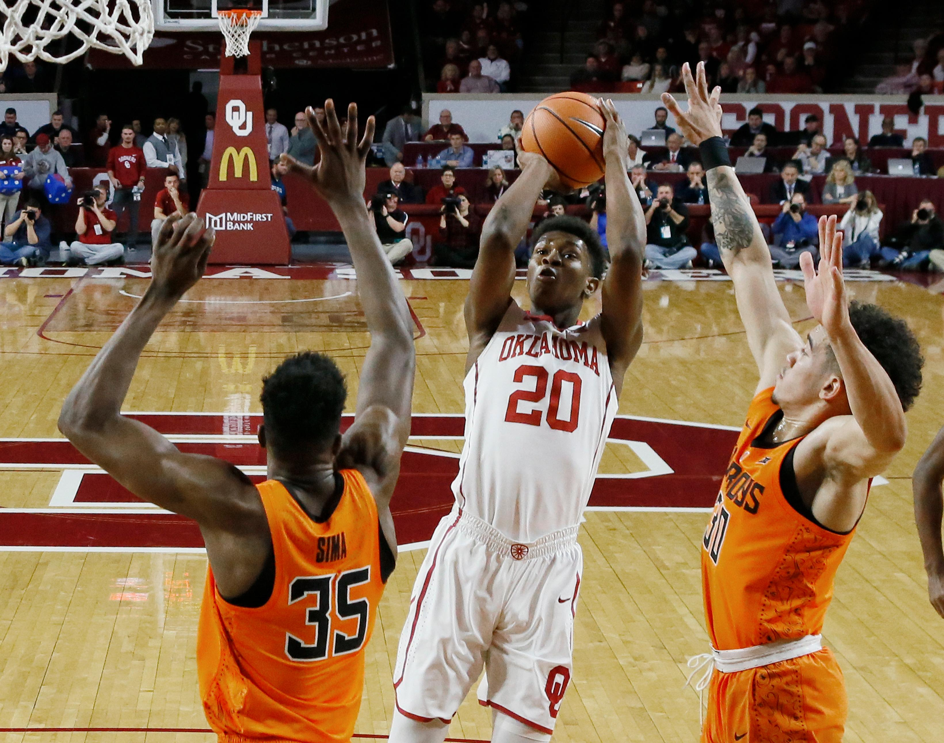 Oklahoma guard Kameron McGusty (20) shots between Oklahoma State forward Yankuba Sima (35) and guard Jeffrey Carroll (30) during the first half of an NCAA college basketball game in Norman, Okla., Wednesday, Jan. 3, 2018. (AP Photo/Sue Ogrocki)